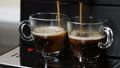 coffee from the coffee machine is poured into glass cups 67529663