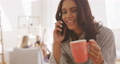 Woman talking on smartphone while holding a cup of coffee 67731687