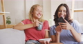 Two young woman friends laughing together while looking in a smart phone 67731691