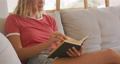 Beautiful woman reading books while sitting on the couch 67731702