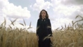 A beautiful woman with dark brown hair in a black dress walks through a wheat field, a summer landscape 67742139