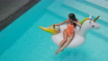 woman is photographing and floating on inflatable unicorn in pool 67784427