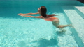 Girl relaxing and swimming in clear water of swimming pool 67784428