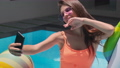 Attractive young lady taking pictures of herself on phone in a swimming pool 67784430