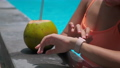 female tourist is controlling smartwatch in pool 67784443