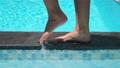 Female feet walking on pool border 67787037