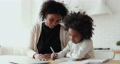 Focused small afro american girl doing homework with smiling mommy. 67817366