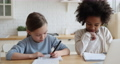 Happy cute little multiracial friends girls doing homework indoors. 67817367