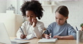 Serious small mixed race children girl handwriting homework, distant learning. 67817374