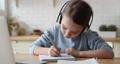 Little primary school girl wearing headphones, doing homework remotely. 67817375