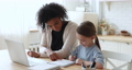 Adult afro american foster parent helping little girl with homework. 67817383