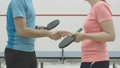 Unrecognizable young man and woman shaking hands in gym in front of table for ping-pong. Handshake of Caucasian sportsman and sportswoman indoors. 67913042