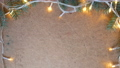 New Years led bulb garland flashes. Decorations of the Christmas tree, a gift with a red ribbon. Wooden table top view of 4k video. 67927663