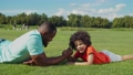 Father and little boy arm wrestling on green grass 67960050