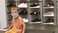 Boy in mask in shoe shop 68345199
