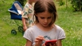 Girl using smartphone near sibling in park 68485294