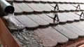 Rain drops falling down on the roof with red tiles during heavy rain storm, slow motion footage clip. 68765024