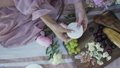 A girl in a pink dress prepares a meal at a picnic in the summer. Cheese, grapes, cherries, nuts, flowers. 68857367