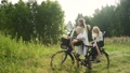Young beautiful happy mother carries two children on a bicycle on the edge of the forest 68857370