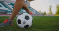 Close up of a male soccer player running with a soccer ball on the football field in the stadium 69100833