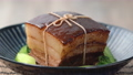 Dong Po Rou (Dongpo pork meat) in a beautiful blue plate with green Qingjiang vegetable, traditional festive food for Chinese new year cuisine meal, close up, panning, rotating, zoom in. 69382773