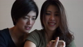 Two Asian woman friends check on their selfie via smart phone 69668542