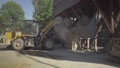 Wide shot of tractor unloading bulk material on production site on sunny day. Machinery working on cement manufacturing factory outdoors. Concrete industry. 69751921