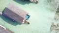 空撮4K俯瞰 水上コテージのプールに横たわる水着姿の女性 69989119