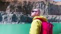 Traveler examines the area. View from the back. Stylish guy with a red backpack dressed in a yellow raincoat stands against the background of a blue lake in a stone canyon. 70190438
