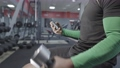 Unidentified black man looks at the phone in the gym while lifting a dumbbell. Sport facilities on the background. Smartphone on hands. 70190445