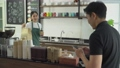 waitress delivers coffee and paper bags to customers at cafe counter. 70309012
