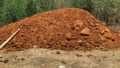 Mountain or pile of red earth on green bush background 70360261