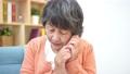 不審な電話に出るシニア女性 70407431
