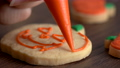 Close up of decorating cute Halloween pumpkin cookies with frosting in icing bag. 70407828