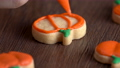 Close up zoom in of decorating cute Halloween pumpkin gingerbread cookies with frosting icing cream topping bag. 70407880