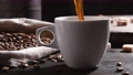 Pouring hot black coffee into mug on table with coffee beans 70507483