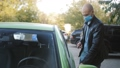 A man gets into her car and removes her protective medical mask during the coronavirus pandemic. 70736604