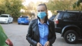 A woman gets into her car and removes her protective medical mask during the coronavirus pandemic. 70736606