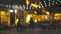 Slow motion shot of illuminated street with cafes and summer terraces. People walk along the pedestrian street of the old city and choose a place for dinner. Cozy restaurants for a romantic evening 70816352