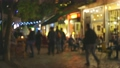 Evening street in the old town with numerous cafes and restaurants. People chat, eat and drink while sitting at cafe tables on summer terraces. Evening city illumination and comfort. Blurred out of 70816356