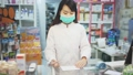 Portrait of chinese female druggist in protective facial mask working in pharmacy 71537751