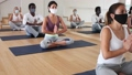 Multiethnic group of sporty people wearing protective masks to prevent viral infections, practicing yoga poses while exercising at fitness center 71537753