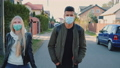 Multiethnic man and woman in medical masks walking down the street in housing estate 71659272