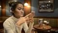 Portrait of young beautiful Asian tourist woman relaxing at the pub indoors 71664556