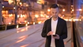 Portrait of young businessman against a city by night using mobile phone 71784341