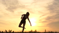 A dancer does a split at sunset, she is in shorts and a tank top in a field at dawn, the action takes place in slow motion 71869159