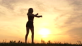 Silhouettes of a blonde girl jumping up in slow motion and makes a dance movement in the air 71869173