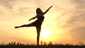 Silhouettes of a girl raises her leg in a dance motion at sunset 71869175