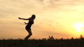 Young girl sportswoman doing the gymnastic wheel with one hand at sunset in slow motion. 71869180