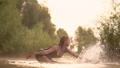 A beautiful wet girl dances in the water standing knee-deep at dawn in the lake with a haze around herself 71869187